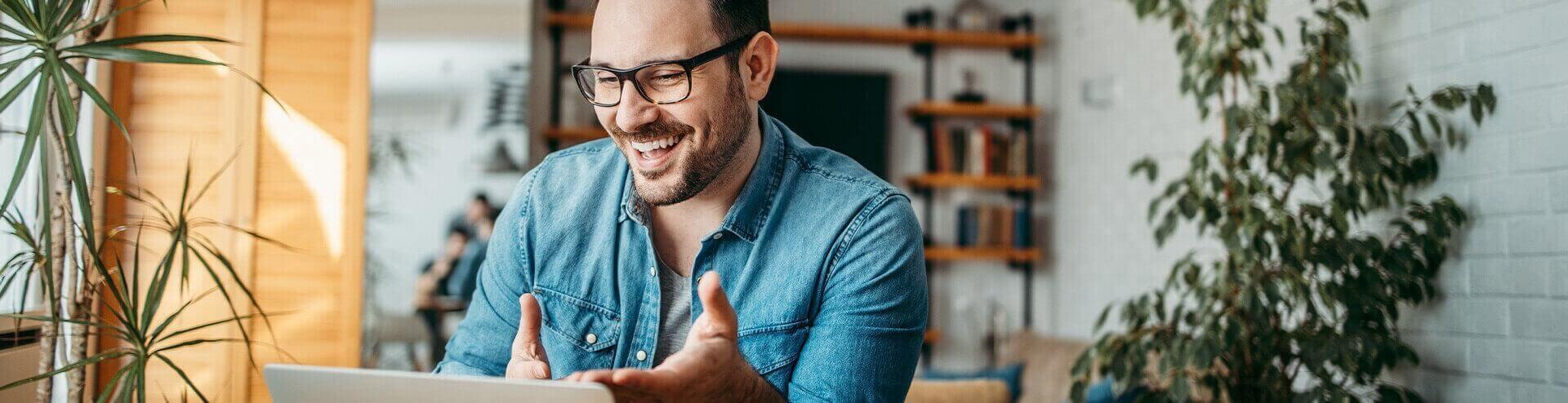 smiling man looking at his laptop