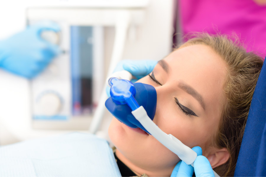 Woman relaxes at the dentist with a nose mask giving her nitrous oxide