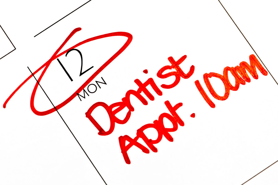 A calendar shows a patient has a dentist appointment in red ink at the dentist in Broken Arrow, OK