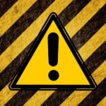 Yellow warning sign on black and yellow stripes to indicate caution